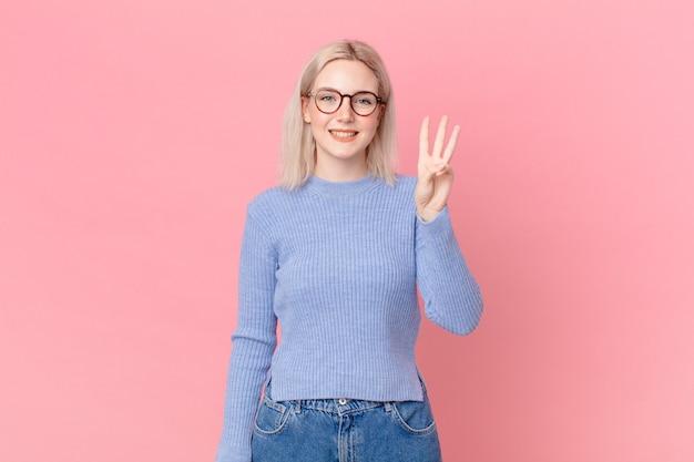 Ładna blond kobieta uśmiecha się i wygląda przyjaźnie, pokazując numer trzy