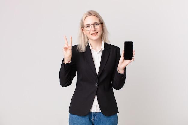 Ładna blond kobieta uśmiecha się i wygląda przyjaźnie, pokazuje numer dwa i trzyma telefon komórkowy