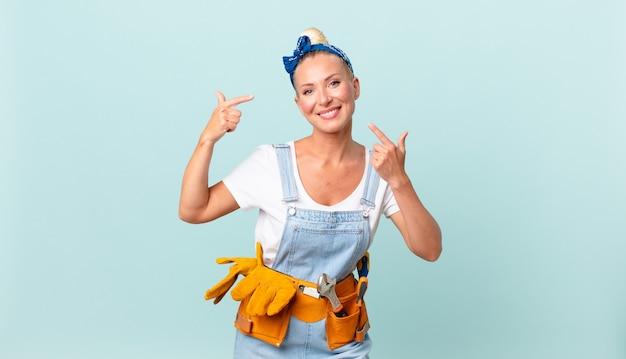 Ładna blond kobieta uśmiecha się pewnie wskazując na własny szeroki uśmiech i naprawia koncepcję domu
