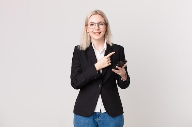 Ładna blond kobieta uśmiecha się radośnie, czuje się szczęśliwa i wskazuje na bok i trzyma telefon komórkowy