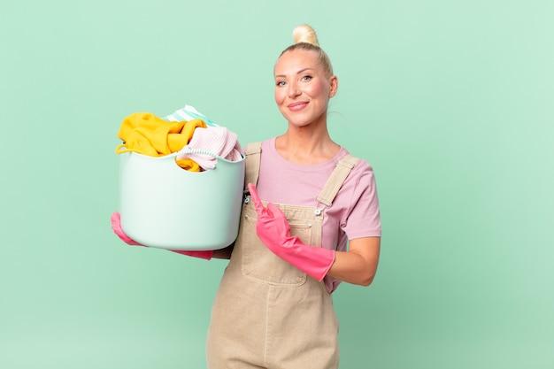Ładna blond kobieta uśmiecha się radośnie, czuje się szczęśliwa i wskazuje na koncepcję prania ubrań z boku