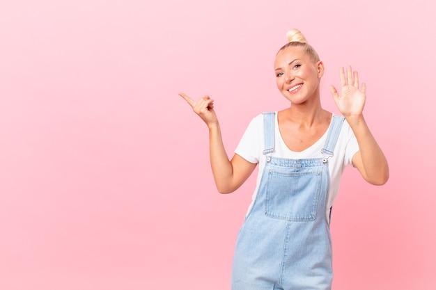 Ładna blond kobieta uśmiecha się radośnie, macha ręką, wita cię i wita