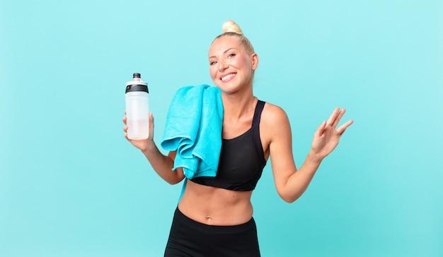 Ładna blond kobieta uśmiecha się radośnie, machając ręką, witając cię i pozdrawiając. koncepcja fitness