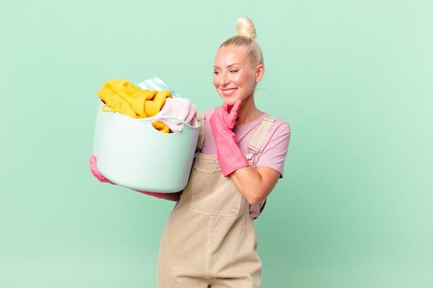 Ładna blond kobieta uśmiecha się ze szczęśliwym, pewnym siebie wyrazem z ręką na koncepcji prania ubrań podbródka