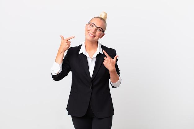 Ładna blond kobieta uśmiechając się pewnie wskazując na swój szeroki uśmiech. pomysł na biznes
