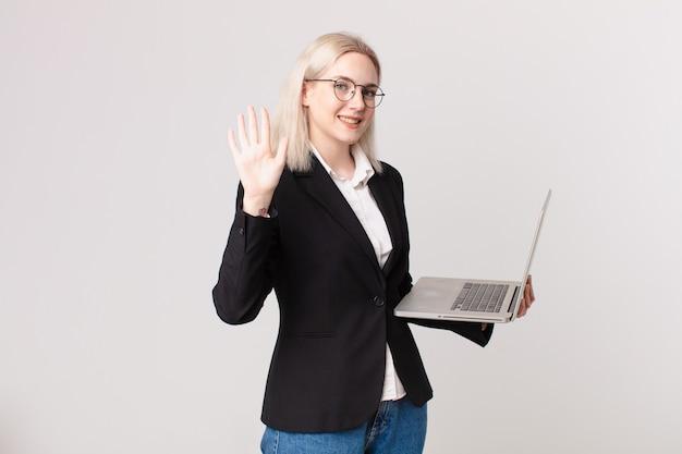 Ładna blond kobieta uśmiechająca się i wyglądająca przyjaźnie, pokazująca numer pięć i trzymająca laptopa