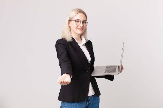 Ładna blond kobieta uśmiechająca się radośnie, oferująca i pokazująca koncepcję i trzymająca laptopa