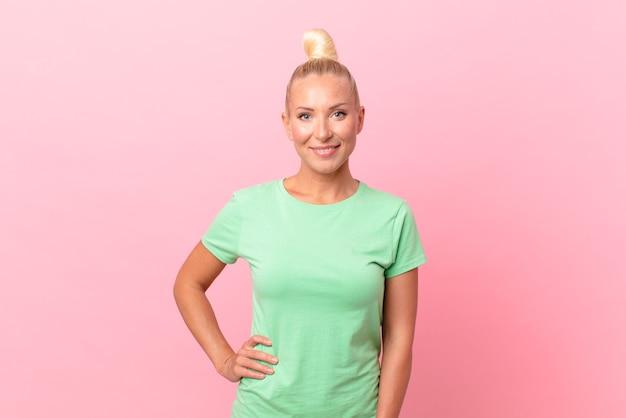 Ładna blond kobieta uśmiechająca się radośnie z ręką na biodrze i pewna siebie