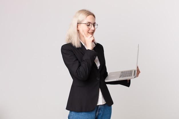 Ładna blond kobieta uśmiechająca się ze szczęśliwym, pewnym siebie wyrazem twarzy z ręką na brodzie i trzymająca laptopa