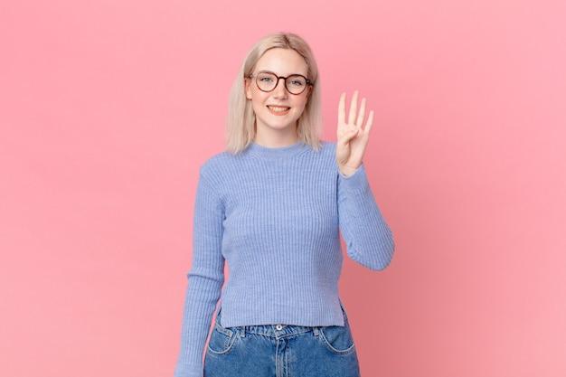 Ładna blond kobieta uśmiechnięta i wyglądająca przyjaźnie, pokazująca cyfrę cztery