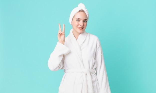 Ładna blond kobieta uśmiechnięta i wyglądająca przyjaźnie, pokazująca numer dwa i ubrana w szlafrok