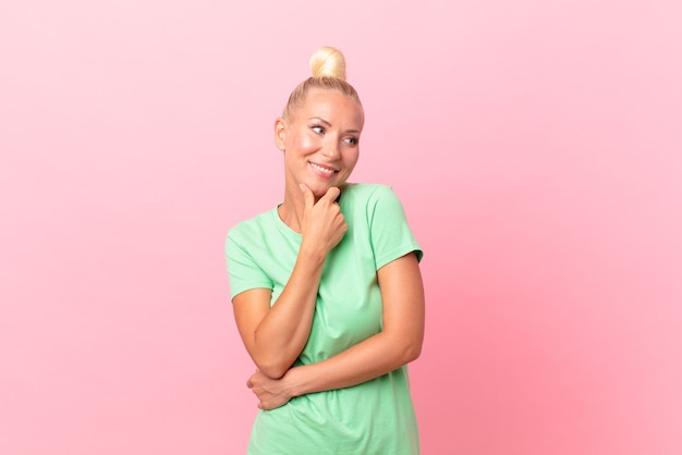 Ładna blond kobieta uśmiechnięta ze szczęśliwym, pewnym siebie wyrazem twarzy z ręką na brodzie