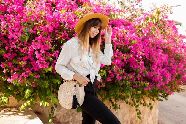 Ładna blond kobieta w słomianym kapeluszu pozuje nad różowym kwitnącym drzewem w pogodnym wiosna dniu