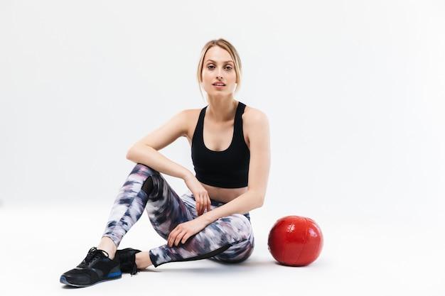 Ładna blond kobieta w wieku 20 lat ubrana w odzież sportową, ćwicząca i wykonująca ćwiczenia z piłką fitness podczas aerobiku na białym tle nad białą ścianą