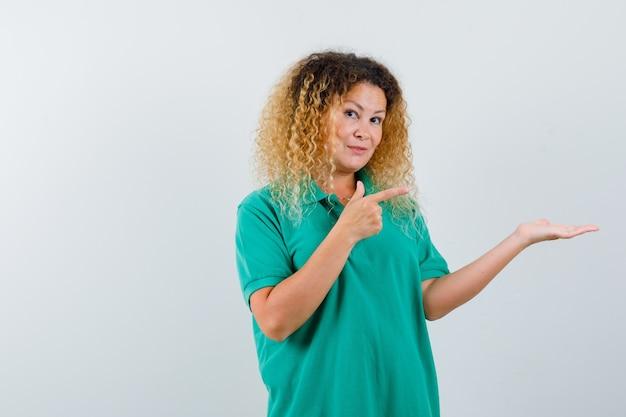 Ładna blond kobieta wskazująca na swoją dłoń w zielonej koszulce polo i wyglądająca wesoło, widok z przodu.