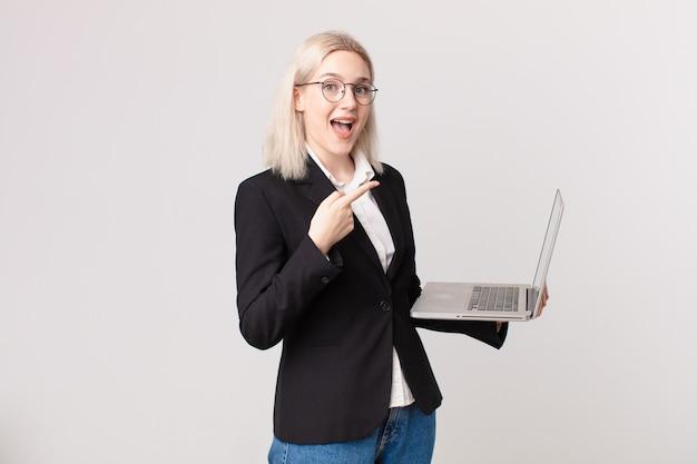 Ładna blond kobieta wygląda na podekscytowaną i zaskoczoną, wskazując na bok i trzymającą laptopa