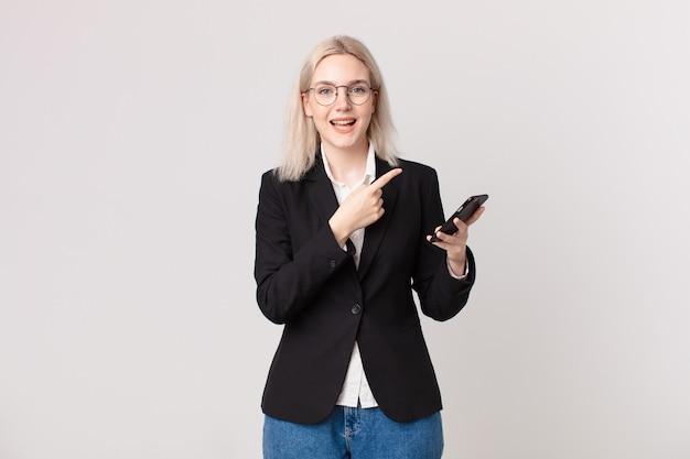 Ładna blond kobieta wygląda na podekscytowaną i zaskoczoną, wskazując w bok i trzymając telefon komórkowy