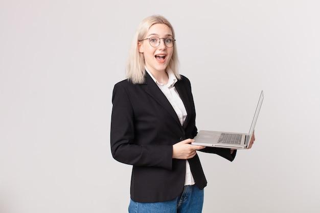 Ładna blond kobieta wygląda na szczęśliwą i mile zaskoczoną, trzymając laptopa