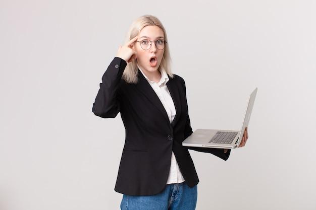 Ładna blond kobieta wygląda na zaskoczoną, realizując nową myśl, pomysł lub koncepcję i trzymając laptopa
