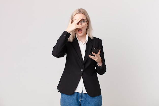 Ładna blond kobieta wygląda na zaszokowaną, przestraszoną lub przerażoną, zakrywa twarz dłonią i trzyma telefon komórkowy