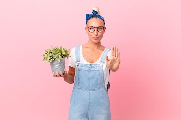 Ładna blond kobieta wygląda poważnie pokazując otwartą dłoń, robiąc gest zatrzymania i trzymając roślinę