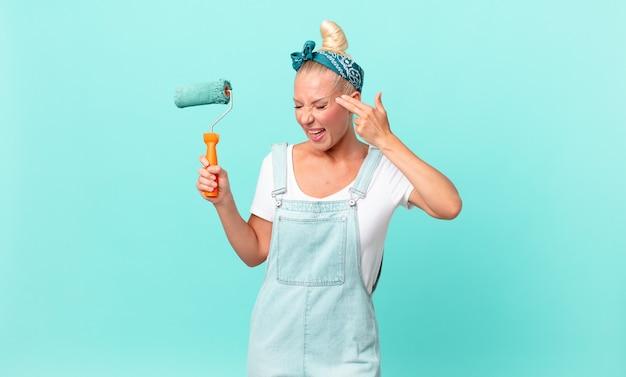 Ładna blond kobieta wyglądająca na nieszczęśliwą i zestresowaną, gest samobójczy, który robi znak pistoletu i maluje ścianę