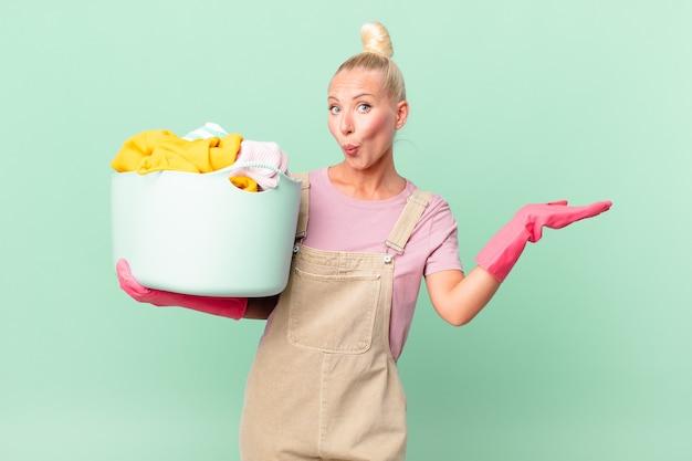 Ładna blond kobieta wyglądająca na zaskoczoną i zszokowaną, z opuszczoną szczęką, trzymającą koncepcję prania ubrań