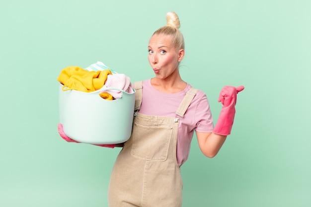 Ładna blond kobieta wyglądająca na zdziwioną niedowierzaniem koncepcji prania ubrań