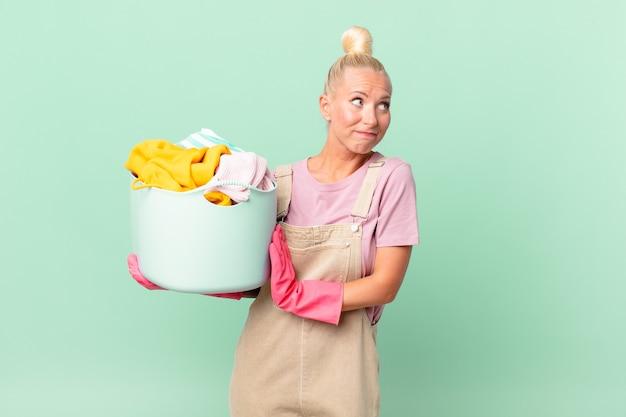 Ładna blond kobieta wzrusza ramionami, czuje się zdezorientowana i niepewna koncepcja prania ubrań