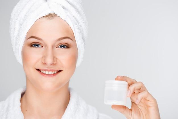 Ładna blond kobieta z kąpielowym ręcznikiem na włosy pokazuje śmietankę