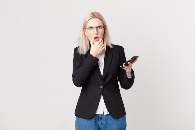 Ładna blond kobieta z szeroko otwartymi ustami i oczami, ręką na brodzie i trzymającą telefon komórkowy