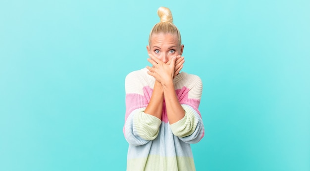 Ładna blond kobieta zakrywająca usta dłońmi w szoku