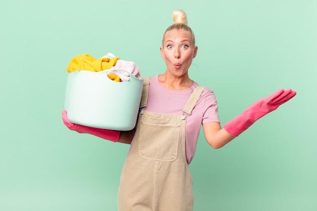 Ładna blond kobieta zdumiona, zszokowana i zdumiona niewiarygodną koncepcją prania ubrań z niespodzianką
