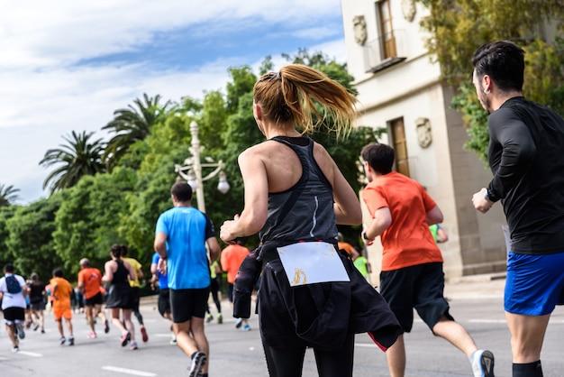 Ładna blond młoda dziewczyna działa ćwiczenia w wyścigu biegowym otoczony przez innych biegaczy.