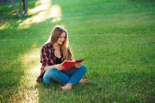 Ładna blond młoda kobieta czyta książkę przy parkiem