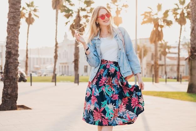Ładna blond uśmiechnięta kobieta spacerująca ulicą miasta w stylowej drukowanej spódnicy i dżinsowej kurtce oversize w różowych okularach przeciwsłonecznych