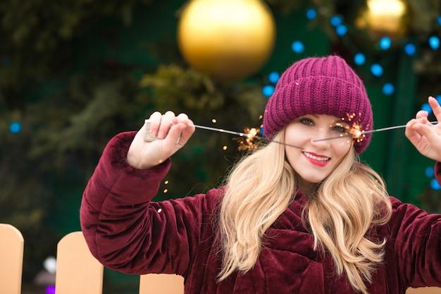Ładna blondynka bawi się błyszczącymi światłami bengalskimi na noworocznym świerku w kijowie