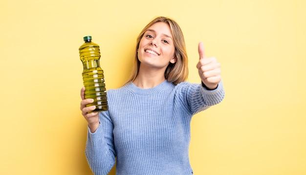 Ładna blondynka czuje się dumna, uśmiechając się pozytywnie z kciukami do góry. koncepcja oliwy z oliwek