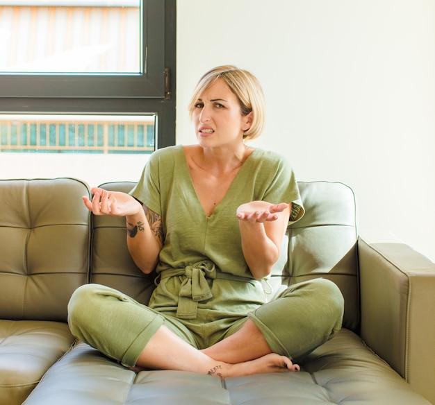Ładna blondynka czuje się nieświadoma i zdezorientowana, nie jest pewna, który wybór lub opcję wybrać, zastanawiając się