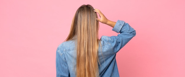 Ładna blondynka czuje się niezorientowana i zdezorientowana, myśląc o rozwiązaniu, z ręką na biodrze, a drugą na głowie, widok z tyłu