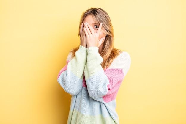 Ładna blondynka czuje się przestraszona lub zawstydzona, zerka lub podgląda z oczami na wpół zakrytymi rękami