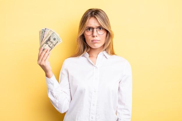 Ładna blondynka czuje się smutna, zdenerwowana lub zła i patrzy w bok. koncepcja banknotów dolarowych