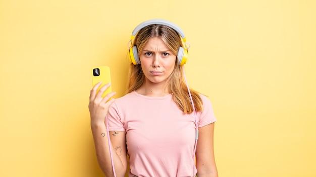 Ładna blondynka czuje się smutna, zdenerwowana lub zła i patrzy w bok. koncepcja muzyki do słuchania