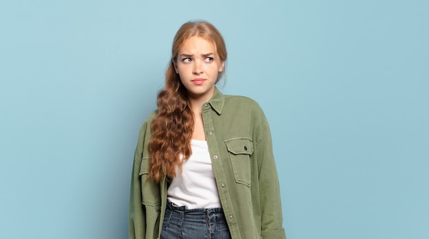 Ładna blondynka czuje się smutna, zdenerwowana lub zła i patrzy w bok z negatywnym nastawieniem, marszcząc brwi w niezgodzie