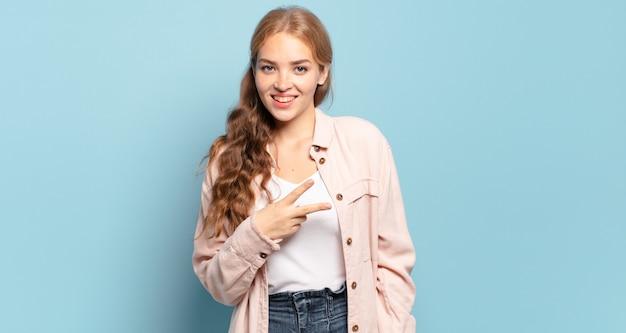 Ładna blondynka czuje się szczęśliwa, pozytywna i odnosząca sukcesy, z ręką tworzącą kształt litery v nad klatką piersiową, pokazując zwycięstwo lub pokój