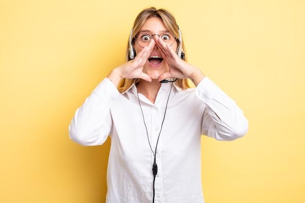 Ładna blondynka czuje się szczęśliwa, wydając wielki okrzyk z rękami przy ustach. koncepcja zestawu słuchawkowego