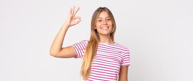 Ładna blondynka czuje się szczęśliwa, zrelaksowana i zadowolona, okazując aprobatę dobrym gestem, uśmiechając się
