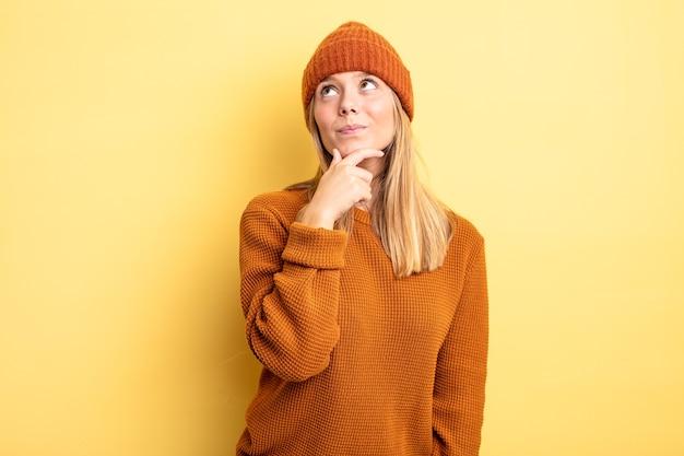 Ładna blondynka czuje się zamyślona, zastanawia się lub wymyśla pomysły, marzy i patrzy na kopiowanie przestrzeni