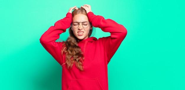 Ładna blondynka czuje się zestresowana i niespokojna, przygnębiona i sfrustrowana bólem głowy, podnosząc obie ręce do głowy