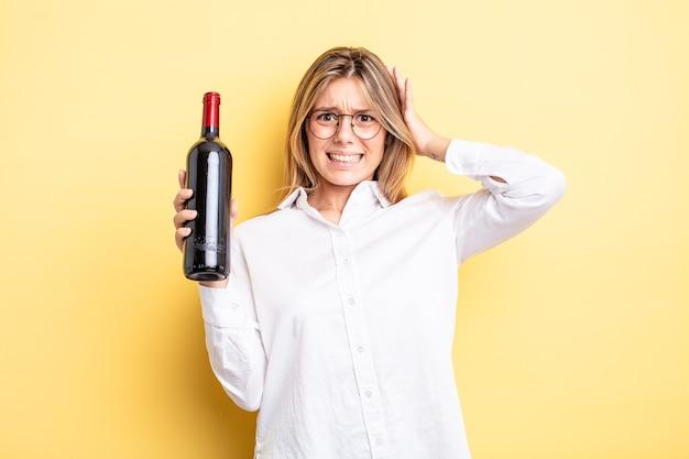 Ładna blondynka czuje się zestresowana, niespokojna lub przestraszona, z rękami na głowie. koncepcja butelki wina